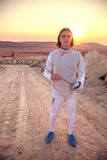 Fencer man wearing white fencing costume holding sword and looking forward Stock Image