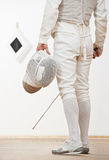 Fencer with mask rapier foil. Fencer in protective sport wear with mask and rapier foil at training stock images