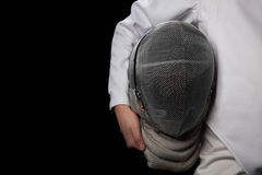 Fencer woman hold her helmet in hand wearing white fencing costume. Isolated on black background. Fencer woman hold the helmet in her hand and wearing white royalty free stock photos