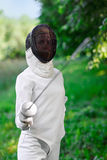 Fencer woman staying over beautiful nature background. With rapier Royalty Free Stock Photo