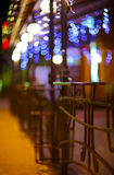 Fences and blurred night lights decorations of the bar on  backg. Round. Christmas time Stock Photography