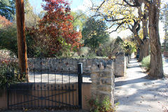 Fences and Walls with Autumn Trees. Autumn trees surround stone walls and steel gates and fences Stock Photography