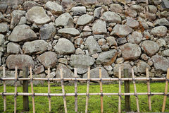 Fench en bambou de poteau, gazon d'herbe et mur en pierre de forme irrégulière Photographie stock