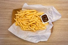 Fench fries and barbecue sauce on white paper on take away paper stock photos