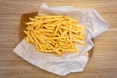 Fench fries on white paper on take away paper tray on w stock images