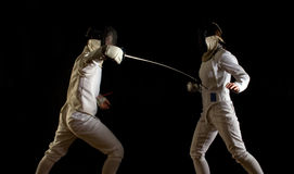 Fencing action. Dramatic action portrait of male and female foil fencers in a bout, scoring a simultaneous touch Stock Photo