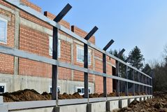 The brickwork of the construction site, columns with metal profiles for the new fence. Fencing construction . The brickwork of the construction site,  columns stock photography