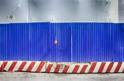 Fencing of construction site with red construction light on the background of blue profiled sheet fence. Fencing of construction site with red construction stock image