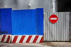 Fencing of construction site with red construction light on the background of blue profiled sheet fence and stop sign. Fencing of construction site with red stock image