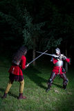 Fencing Duel Between Two Knights in Armor in the Forest Stock Photography