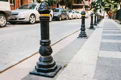 Fencing pillars barriers in a row between the road and the pedestrian zone in the residential quarter of the city.  Royalty Free Stock Image