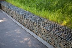 Fencing of stones covered with galvanized metal mesh in the summer Park stock images