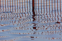Fencing in the water. Rusty fence in the water with a beautiful reflection of the Stock Images