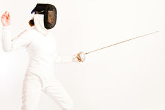Fencing Woman. Woman dressed in a fencing suit and mask, pointing her rapier. side view royalty free stock images