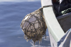 Fender ball hanging of a fisher boat with blue sea Stock Photos