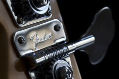 Fender Brand on Bass Guitar tuning peg. Bath, United Kingdom - May 13, 2011: Fender brand name chased into a metal tuning peg on a Jazz Bass guitar with a black Stock Images