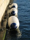 Fender buoys on canal bank. Row of protective fender buoys on canal bank royalty free stock photos