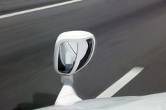 A fender mirror on the car while driving on a highway Royalty Free Stock Photography