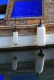 Fender zwei auf einem alten Boot mit Reflexion im Wasser Stockfoto