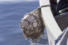 Fenderballhängen eines Fischerbootes mit blauem Meer Stockfotos