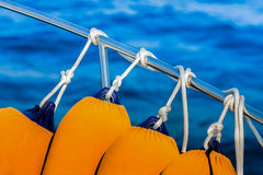 Fenders Anchored To The Guardrail. Fenders coated in yellow anchored to the boat guardrail, against blue water Stock Photography