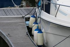 Fenders on a yacht in a marina. Fenders out on a yacht on a marina pontoon Royalty Free Stock Image