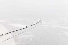 Fendi nel ghiaccio su un lago congelato coperto di neve Fotografie Stock Libere da Diritti