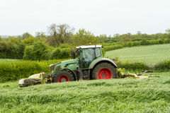 Fendt green tractor with claas mowers in silage field. Fendt green tractor with claas mowers mowing grass for silage in english field Stock Photography