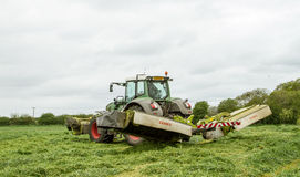 Fendt green tractor with claas mowers in silage field. Fendt green tractor with claas mowers mowing grass for silage in english field Stock Photo