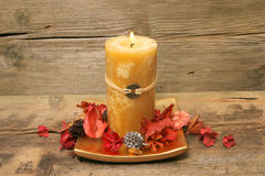 Feng Shui candle and pot pourri. Fe ng Shui candle and pot pourri on a background of old weathered wood stock photo