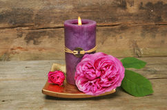 Feng Shui candle and rose. Feng Shui candle and red rose on a background of old wood stock photo