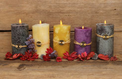 Feng Shui candles. Five burning Feng Shui candles and potpourri on a background of old weathered wood royalty free stock photography