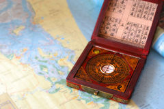 Feng shui compass on a nautical chart. Classic feng shui compass juxtaposed on a modern nautical chart Stock Images