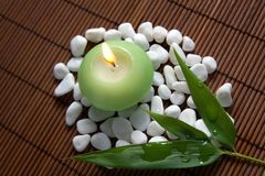 Feng-shui composition. Burning candle, white stones and bamboo leaves - composition for meditation and inner harmony royalty free stock photo