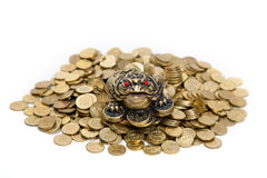 Feng Shui Frog sitting on the heap of coins. Feng Shui Frog sitting on the heap of Kazakh coins at white background stock photography
