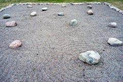 Feng Shui garden zen stones. Circular line in Feng Shui garden zen stones on a background of small pebbles royalty free stock photo