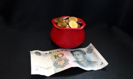 Feng Shui Red Coin Pot. On black satin Stock Photo