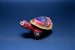 Red feng-shui turtle colored metal with detachable carapace shell for jewelry depositing on dark background. A feng-shui red turtle colored metal with detachable royalty free stock photo