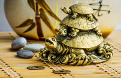Feng-shui turtles. Gold feng shui turtles statuette on a bamboo mat royalty free stock photo