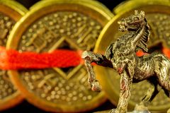 Feng shui year of the Horse. With figure of a horse and chinese coin chain Stock Photography