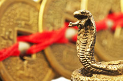 Feng shui year of the snake. With chinese coins and a snake figure royalty free stock photo