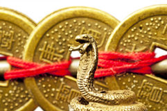 Feng shui year of the snake. With chinese coins and a snake figure Stock Photo