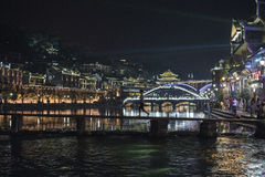 Fenghuang Ancient Town. FENGHUANG, CHINA - SEPTEMBER 16, 2015: View of boats full of tourists and Hong Rainbow bridge in Fenghuang, China Royalty Free Stock Photography