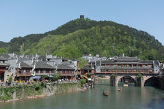 Fenghuang ancient travel town in China. FENGHUANG - April 13:Wooden boats with tourists at Fenghuang ancient town on April 13, 2015 in Fenghuang,China.Fenghuang stock photo
