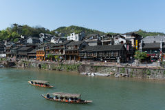 FENGHUANG - April 13:Wooden boats with tourists at Fenghuang anc. Ient town on April 13, 2015 in Fenghuang,China.Fenghuang ancient town was added to UNESCO World Stock Image