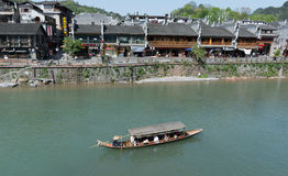 FENGHUANG - April 13:Wooden boats with tourists at Fenghuang . FENGHUANG - April 13:Wooden boats with tourists at Fenghuang ancient town on April 13, 2015 in stock photos