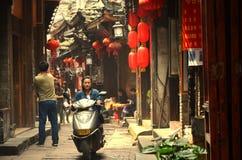 Fenghuang, China - 15. Mai 2017: Frau auf Motorrad auf Straße in der Stadt Phoenix Fenghuang Stockbild