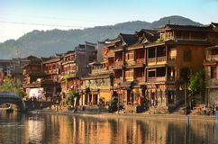 Fenghuang, China - May 15, 2017: Old building with people in food court on riverside near Phoenix Hong Bridge in Fenghuang Stock Photos