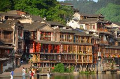 Fenghuang, China - May 15, 2017: Old building with people in food court on riverside near Phoenix Hong Bridge in Fenghuang Royalty Free Stock Photos
