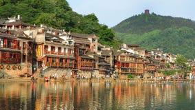 Fenghuang, China - Mei 15, 2017: De oude bouw met mensen in voedselhof op rivieroever dichtbij Phoenix Hong Bridge in Fenghuang Royalty-vrije Stock Afbeeldingen